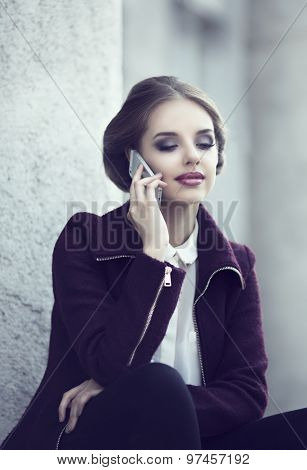 beautiful elegant woman with cellphone outdoor in the street