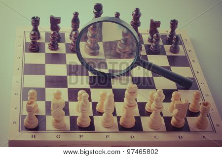 Chess Game Strategy With Chess Pieces And Magnifying Glass, Vintage Style