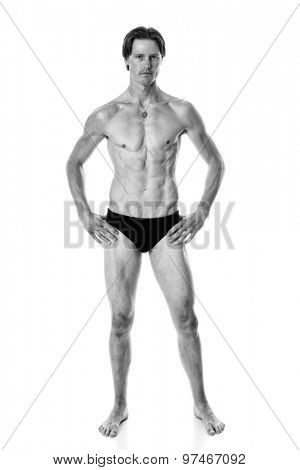 Man in swimwear. Studio shot over white. Black and white.