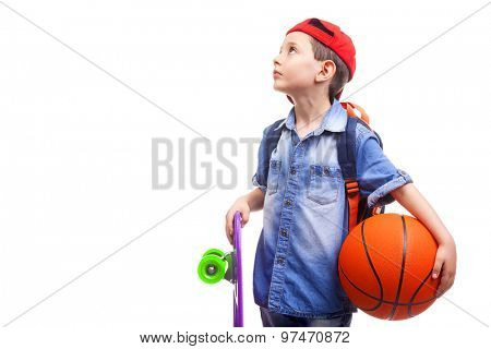 Pensive school boy holding a skateboard and a basketball on white background