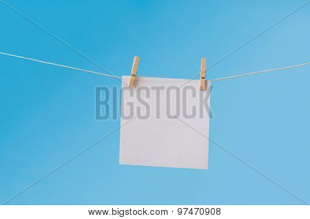 Blank Note Paper Pegged On Clothes Line Against Blue Sky