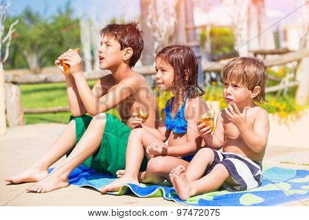 Happy children on the beach, three little best friends resting near the pool and eating croissants, enjoying active summer holidays