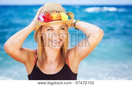 Portrait of happy beautiful woman wearing wearing stylish beach hat on blue sea background, enjoying active summer holidays