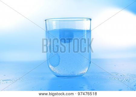 Pill in glass of water on light background