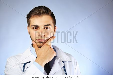 Male doctor with stethoscope on blue background
