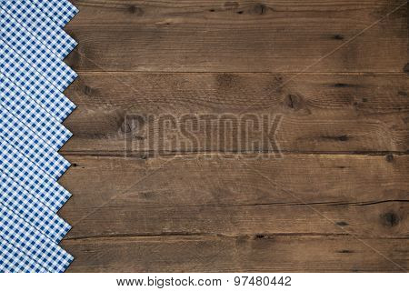 Old wooden brown background in bavarian style with a blue white checked border.