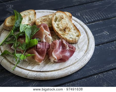 ham, ciabatta, fresh arugula on a wooden Board on a dark surface