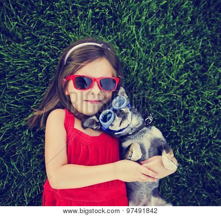 snapshot of a cute girl with sunglasses holding a chihuahua with goggles on in a grassy park or yard with a lawn toned with a retro vintage instagram filter effect app or action (focus on the dog)