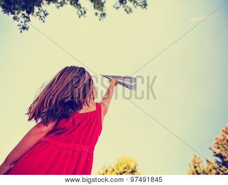 a cute girl in a red dress throwing a paper airplane into the sky while a real plane is passing overhead in a park during summer time toned with a retro vintage instagram filter app or action effect
