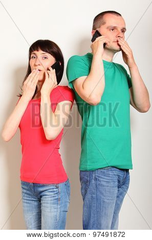 Shocked Woman And Man Talking On Mobile Phone