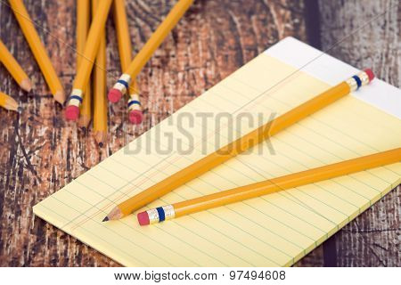 Group Of Yellow Pencils And Notepad On Vintage Wooden Desk