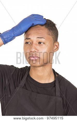 Closeup hispanic young man wearing blue cleaning gloves facing camera with right arm raised