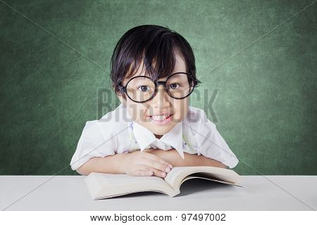Attractive Kid Reads Book On Desk In The Class
