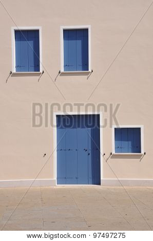Closed blue windows and door on wall of mediterranean house