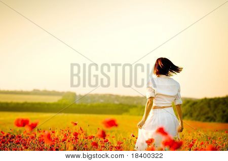 Girl stands in poppy field