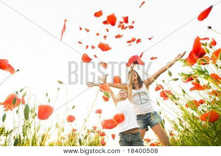 mother and son stand in poppy field