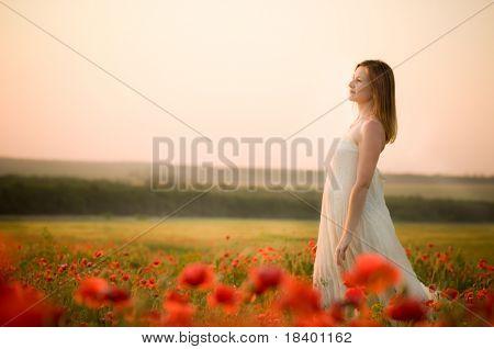 woman stands in poppy field