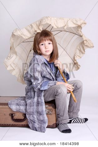 Little girl with umbrella sitting on a suitcase