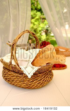 Table setting with bread basket outdoors with wine bottles on background
