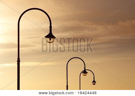 Three street lanterns over the orange sunset sky