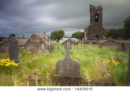 Irish graveyard at Dingle peninsula old ruins of church long exposure gives moody feel caused by blurry vegetation and clouds