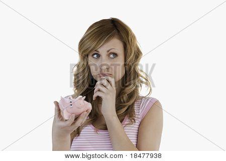 Blond-haired Woman Perplexed Concerning Her Broken Piggybank