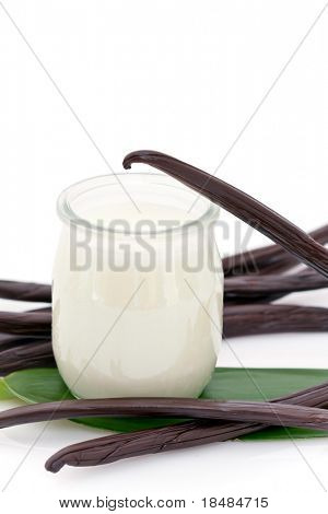 Glass container of togurt with fresh vanilla beans and leaf on white background