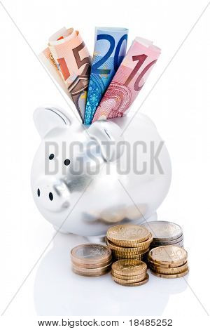 Euro bank notes in slot of piggy bank with piles of coins in foreground, isolated on white.