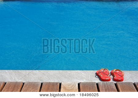 Sandals by the swimming pool. Concept: Summer vacation by the beach