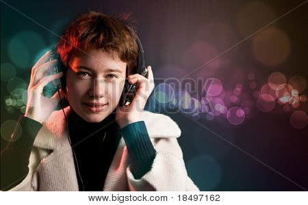 Pretty woman deejay enjoying music on dance floor with colorful bokeh background
