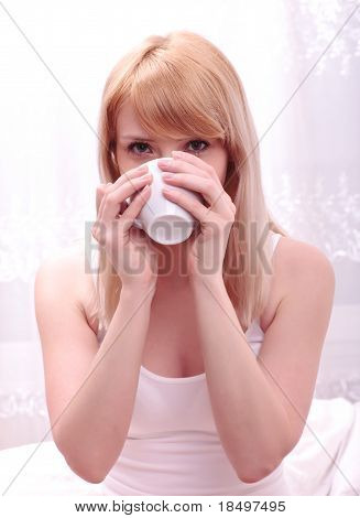 Cute Woman Drinking A Coffee Sitting On Her Bed