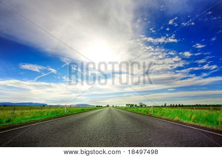 Road going straight ahead under spectacular blue cloudy sky