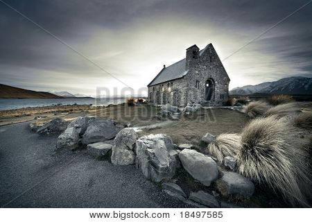 Small church in New Zealand with lake and mountains in background