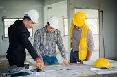 Management Consulting And Engineers And Foreman Working With Blueprint And Drawing On Work Table For poster