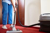 Hotel maid cleaning carpet with vacuum cleaner poster