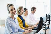 Team of customer service executives working in call center poster