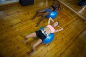 Two fit women performing pilate on exercise ball in fitness studio poster