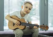 Young boy play on guitar at home at sunny day. Boy play on ukulele - hawaiian guitar. poster
