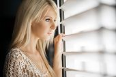 Beautiful young woman looks out through blinds