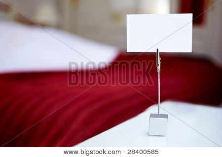 Empty white card on a card holder in a hotel room