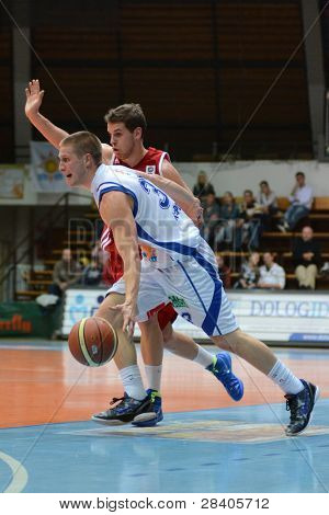 KAPOSVAR, HUNGARY - NOVEMBER 19: Nik Raivio (in white) in action at a Hugarian National Championship  basketball game Kaposvar (white) vs. Paks (red) November 19, 2011 in Kaposvar, Hungary.