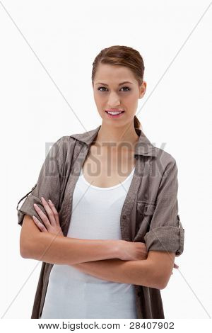 Smiling woman standing with folded arms against a white background