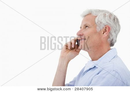 Side view of a mature man making a phone call against a white background