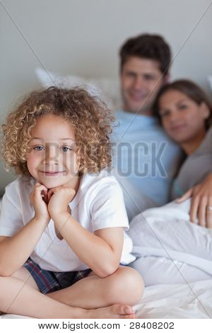 Portrait of a boy sitting on his parents's bed while looking at the camera