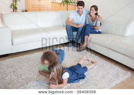Children using a tablet computer while their happy parents are watching in their living room
