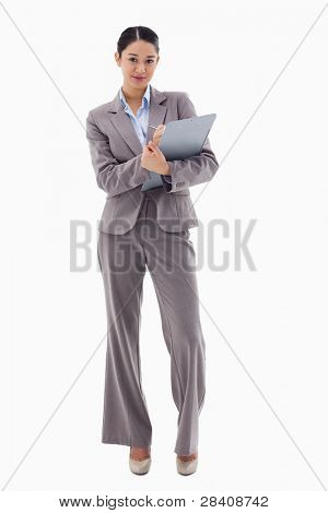 Portrait of a brunette businesswoman taking notes against a white background