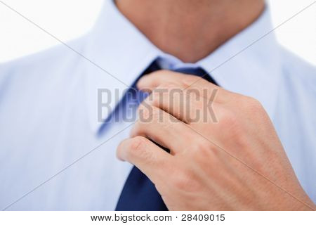 Close up of a hand fixing a tie against a white background
