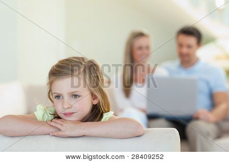 Thoughtful girl with her parents behind her