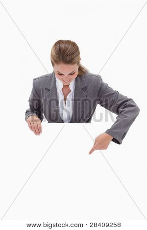 Bank employee pointing down at blank sign in her hands against a white background