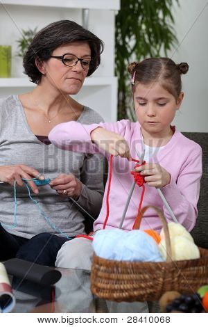 Grandmother teaching a little girl to knit